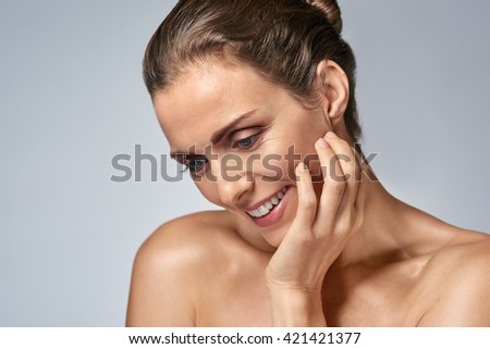 Middle age beauty model looking down in studio, healthy mature woman - stock photo