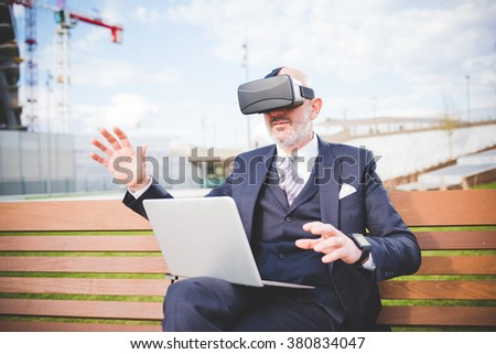 Middle age caucasian business man sitting on a bench with laptop on his knee using smart watch and 3D viewer - futuristic, multitasking, technology concept - stock photo