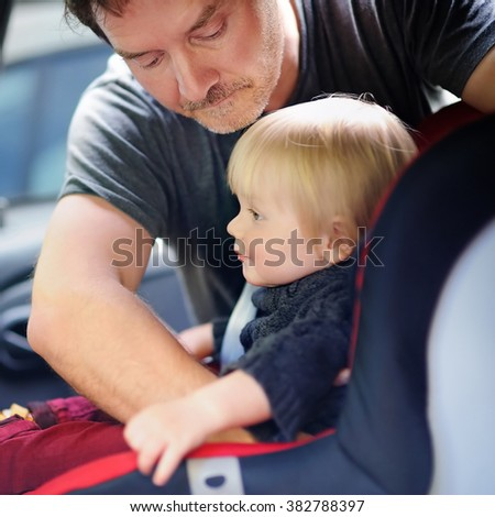 Middle age father helps his toddler son to fasten belt on car seat, focus on father  - stock photo
