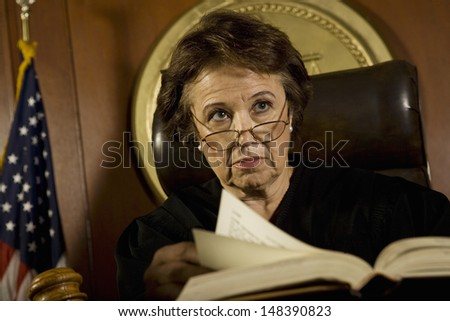 Middle age female judge with book looking away in court room - stock photo