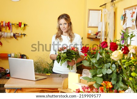 MIddle age florist standing at her small flower shop while holding a bunch of flower.  - stock photo