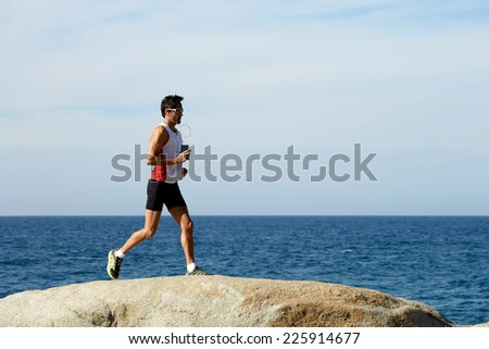 Middle age man at workout outdoors jogging along the sea at sunny day - stock photo