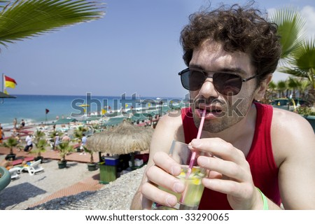 middle-age man in glasses drink cocktail Mojito on beach - stock photo