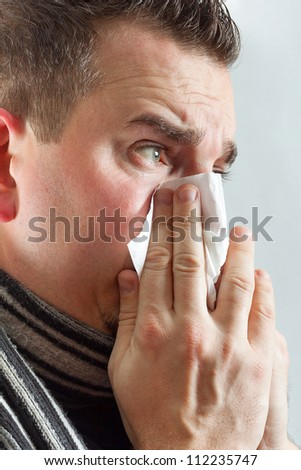 Middle age man with cold holding tissue - stock photo