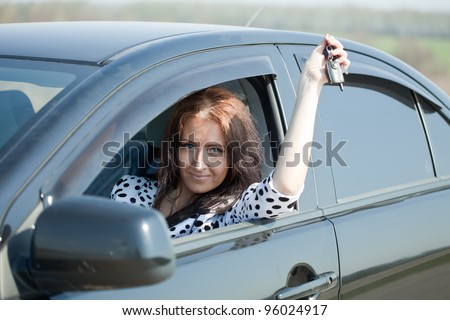 middle age woman holding keys to new car - stock photo