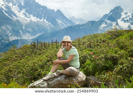 Middle age woman rests on stone in high mountains - stock photo
