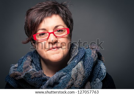 Middle age woman with red glasses close up portrait on dark background. - stock photo