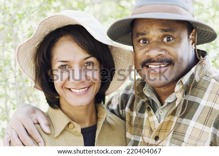 Middle-aged African couple smiling outdoors - stock photo