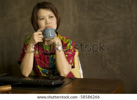 Middle aged Asian woman sitting at her desk with a cup of tea and relaxing - stock photo