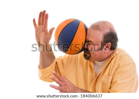 Middle-aged balding man with a goatee playing sport being hit by a Illinois basket ball with force in the face when he misses a catch or as an unexpected accident to a spectator, on white. - stock photo