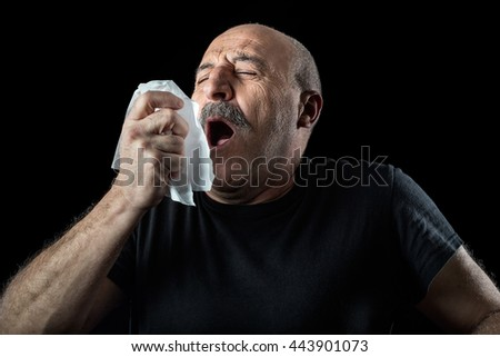 Middle-aged balding man with seasonal flu or allergy sneezing into a handkerchief, head and shoulders over a black background - stock photo