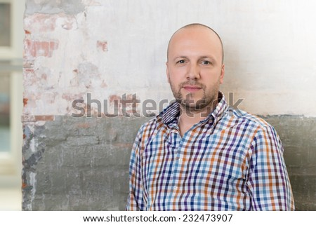 Middle-aged bearded man standing in front of a grunge wall looking at the camera with a quiet smile, head and shoulders portrait - stock photo