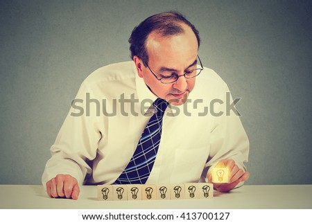 Middle aged business man sitting at table desk with yellow bright light bulb idea. Concept of innovation and problem solving   - stock photo