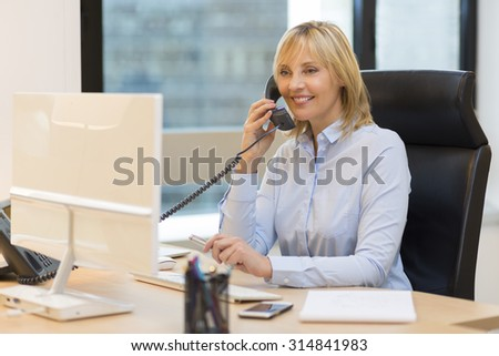 Middle aged business woman using phone at office - stock photo