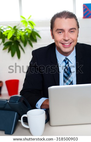 Middle aged businessman at his work desk - stock photo