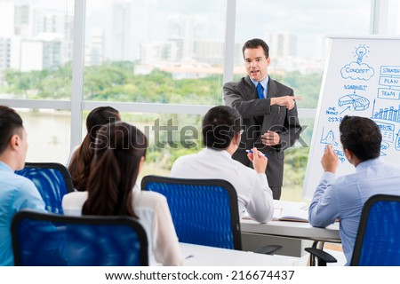 Middle-aged businessman conducting seminar for his colleagues - stock photo