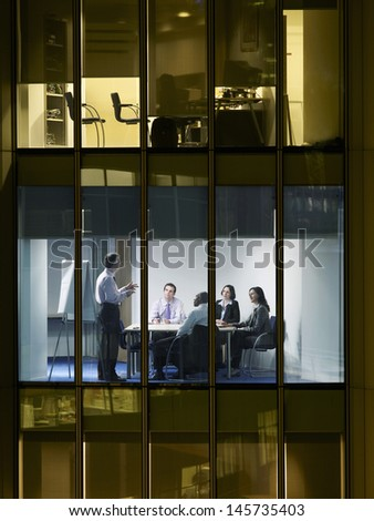 Middle aged businessman giving presentation to colleagues in meeting room at night - stock photo