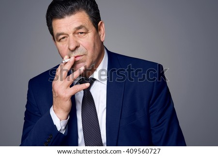 middle aged businessman in a blue suit smokes - stock photo