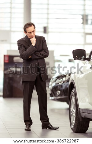 Middle aged businessman in classic suit is examining a car while standing in a motor show - stock photo