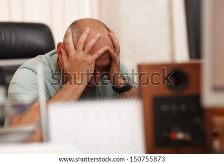 Middle-aged businessman in the office thinking about business problems - stock photo