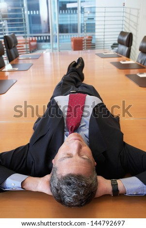 Middle aged businessman lying on conference table at office - stock photo