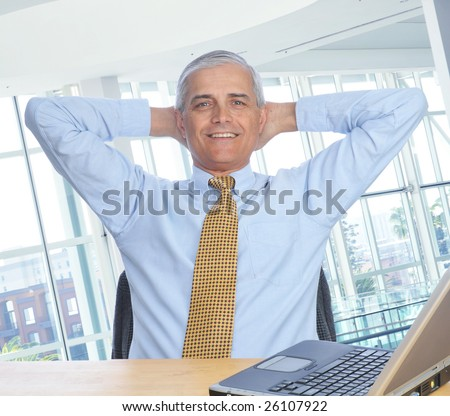 Middle Aged Businessman sitting at his desk with his hands behind his head - stock photo