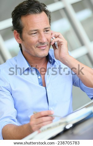 Middle-aged businessman talking on smartphone - stock photo