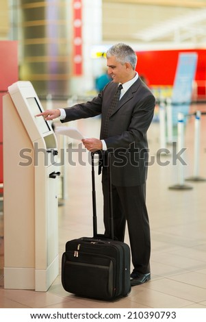 middle aged businessman using self help check in machine at airport - stock photo