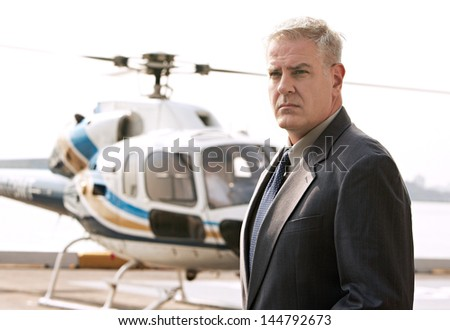 Middle aged businessman waiting at the helicopter pad - stock photo