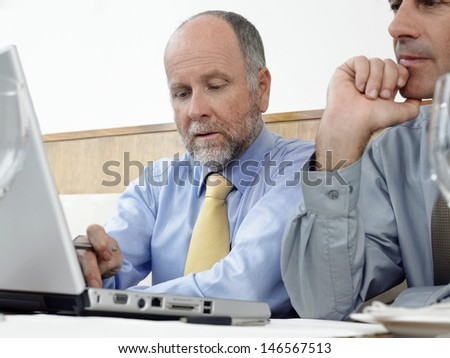 Middle aged businessman with colleague using laptop in restaurant - stock photo