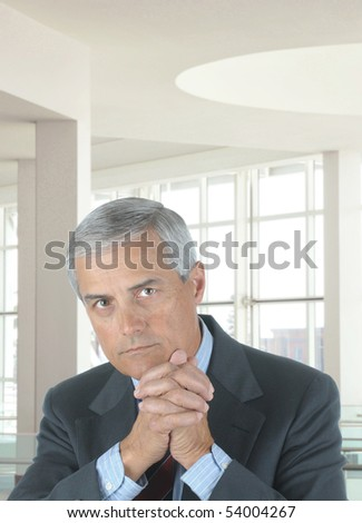 Middle aged businessman with serious expression seated at his desk in modern office with hands in front of face. - stock photo
