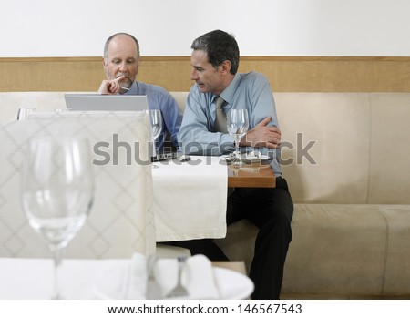 Middle aged businessmen using laptop in restaurant - stock photo