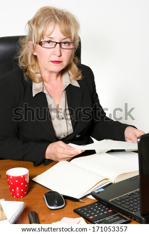 Middle aged businesswoman, at the desk in the office. - stock photo