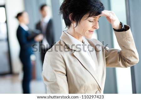 middle aged businesswoman having headache in office - stock photo