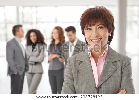 Middle-aged businesswoman in front, business team talking in background. - stock photo
