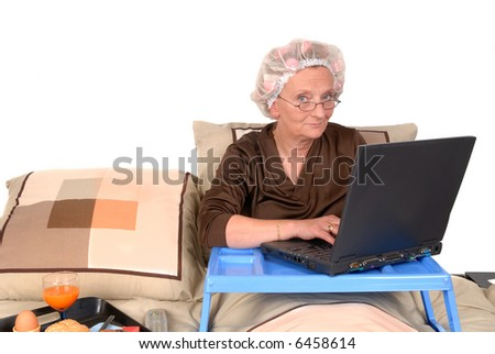 Middle aged businesswoman in pyjamas working at home in bed, laptop on tray.  Tray with breakfast on the side - stock photo