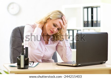 middle-aged businesswoman with headache having stress in the office - stock photo