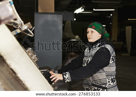 Middle-aged caucasian woman controls the process while looking at machine - stock photo