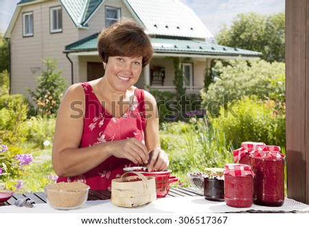 Middle aged Caucasian woman making home made jam from berries  - stock photo