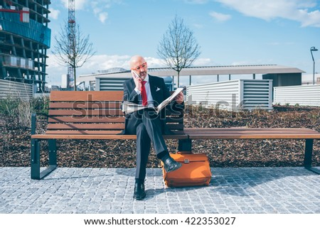 Middle-aged contemporary businessman sitting on a bench outdoor in the city reading newspaper talking smart phone - work, conversation, information concept - stock photo