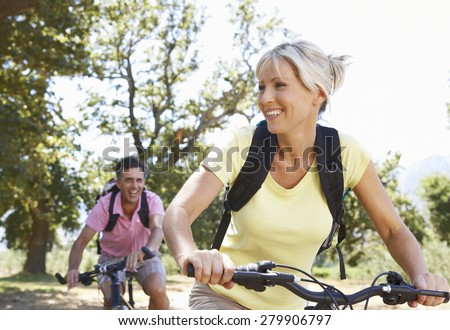 Middle Aged Couple Cycling Through Countryside - stock photo