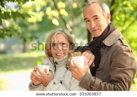 Middle-aged couple drinking coffee in park - stock photo