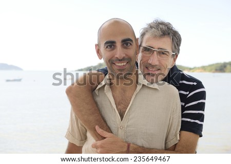 Middle aged couple gay couple on vacation - stock photo