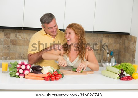 Middle-aged couple happy smiling behind the table in the kitchen. Cheerful husband and wife preparing summer delicious dishes. - stock photo