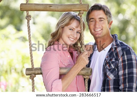 Middle Aged Couple In Garden By Treehouse - stock photo