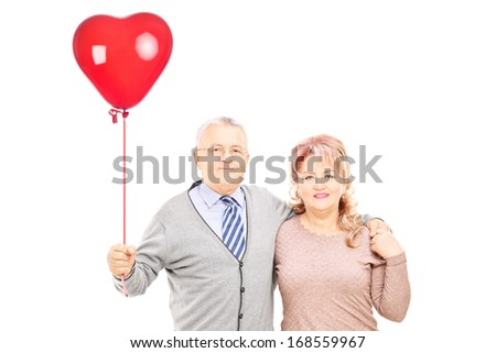Middle aged couple in hug holding a red heart balloon isolated on white background - stock photo