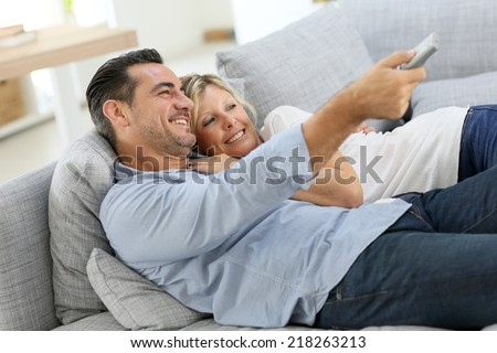 Middle-aged couple in sofa watching tv - stock photo