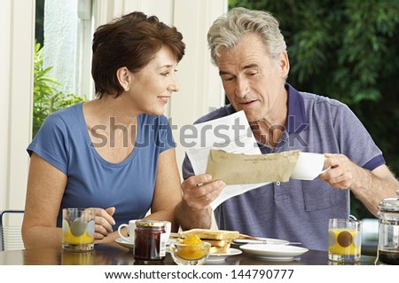 Middle aged couple looking at bills over breakfast in the house - stock photo