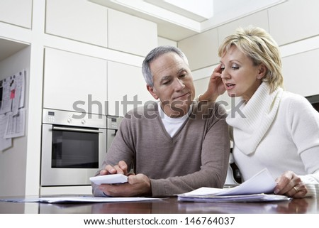 Middle aged couple making calculations using calculator at kitchen table - stock photo