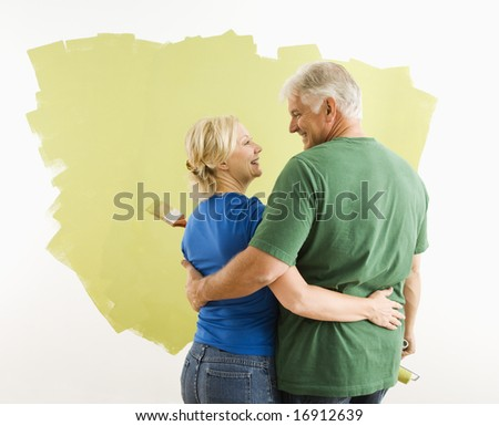 Middle-aged couple painting wall green observing and discussing their work. - stock photo